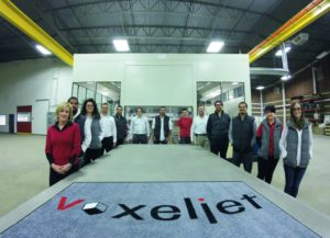Das Team von Voxeljet America steht zum Größenvergleich an der 4000 mm langen Bauplattform - im Hintergrund die VX4000.